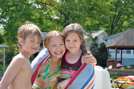 three children dry off after spending the day swimming