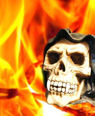 canine: horror skull with canine teeth on fire background