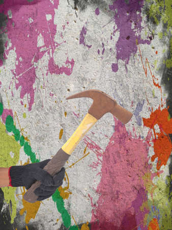 hammer in a hand with black glove on defected concrete panel background or texture