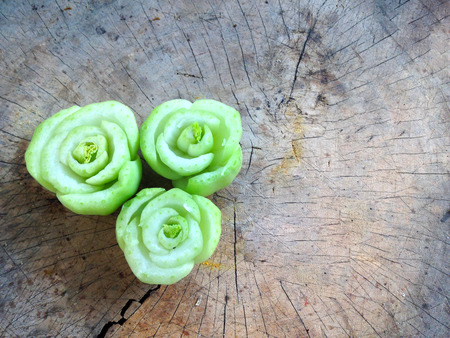 roses from rearrange of cutting lettuce on wooden plate or chopping block