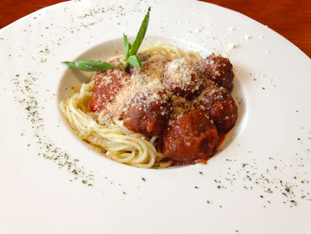 spaghetti meatballs with basil and parsley on white plate