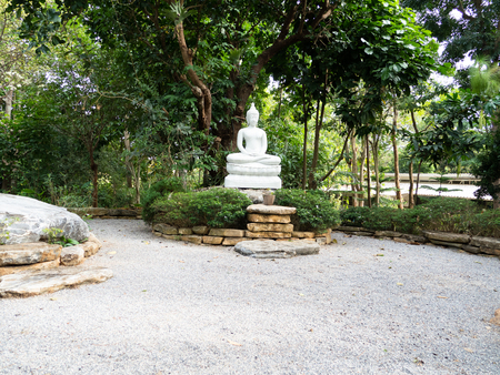 white statue of buddha in the center of pebble court Stock Photo