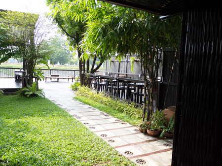 sitting area in the shady garden with pavement and trees