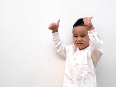 very happy asian boy making thumbs up sign and smiling happily on white background with paper space