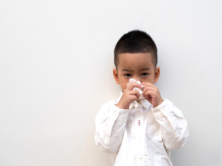 sick asian boy blow his nose into tissue on white background and paper space