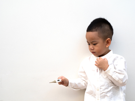 sick asian boy with thermometer in hand on white background and paper space