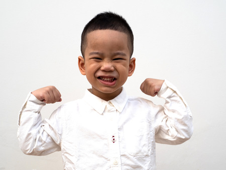 little smiling asain boy show his strength and good health on white background