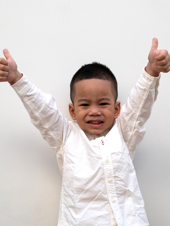 very happy asian boy making thumbs up sign and smiling happily