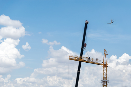 crane erecting platform to start construction of a building structure with an airplane crossing in background Imagens