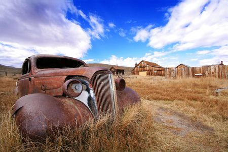 ghost town: Rusted Classic Auto and Ghost Town Stock Photo
