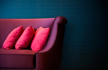 idea comfortable: Three red decorative pillows on a contemporary sofa.  Stock Photo