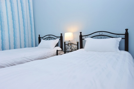 Two beds bedroom with bedside table and lamp   photo
