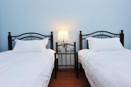 gemelas: Dos camas de un dormitorio con mesita de noche y lámpara