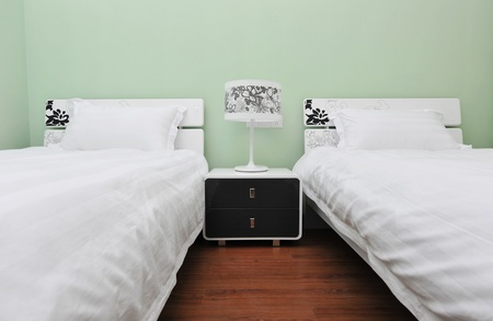 'bedside table': Two beds bedroom with bedside table and lamp.