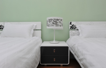 twin house: Two beds bedroom with bedside table and lamp.