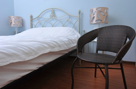 bedchamber: bed and chair in the bedroom. Stock Photo