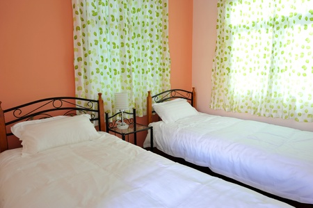 bedside: Two beds bedroom with bedside table and lamp.