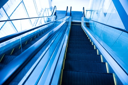 Perspective of escalator toned in blue color.  photo