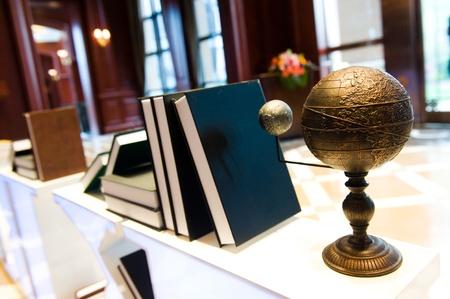 vintage world globe and many books sitting on a desk.  photo