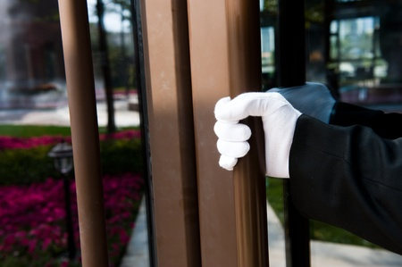 hotel service: The hotel waiter opening the door for customers.
