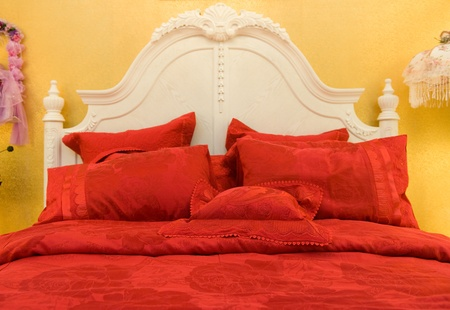 hotel suite: Double bed with pillows in red color.
