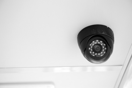 security camera: A security camera peers down from the top of building.