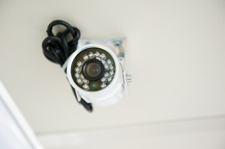A security camera peers down from the top of building. photo