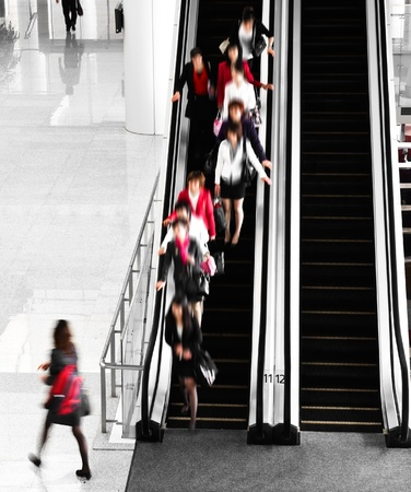 People rushing on escalator in business center, mall or airport to work,  with motion blur .
