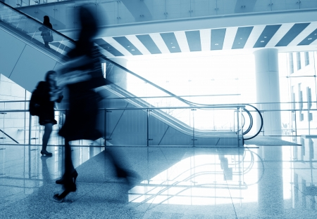 moving activity: People rushing on escalator in business center, mall or airport to work,  with motion blur .  Editorial