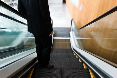 conveyor rail: businessman going down the escalator.Motion blur