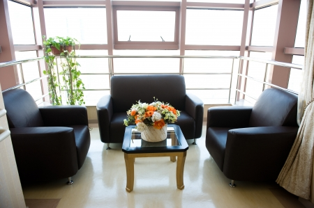 Hospital or clinic waiting room with empty chairs and table.