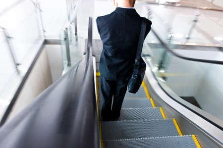 conveyor rail: businessman going down the escalator.Motion blur