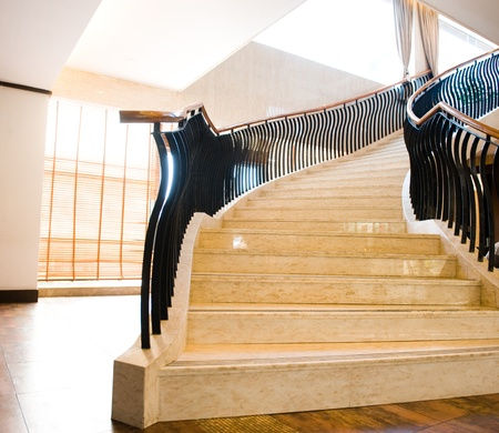 Interior of hotel with marble staircase and banisters.