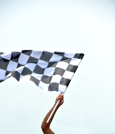 checkered race flag in hand. Stock Photo - 13344618