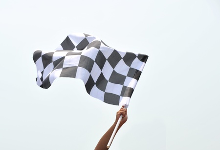 checkered race flag in hand. Stock Photo - 13344616