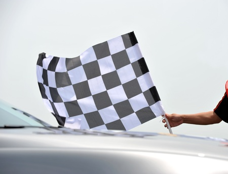 checkered race flag in hand. Stock Photo - 13344624