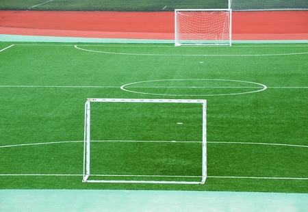 dividing: Empty soccer field with goal posts and light poles. Stock Photo