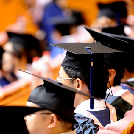 mba: Graduating class in caps and gowns at commencement.