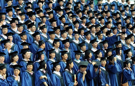 academic achievement: Graduating class in caps and gowns at commencement. Editorial
