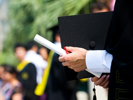 education goals: graduating student holding their diploma proudly.  Stock Photo