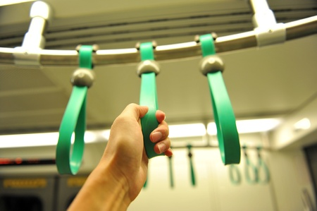 handle bars: people holding onto a handle on a train.