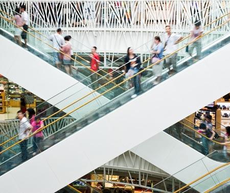 plaza comercial: Gente en movimiento en las escaleras mec�nicas en el moderno centro comercial.