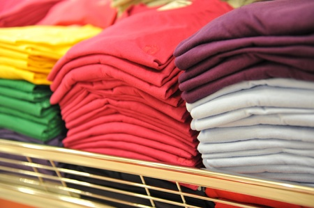 Colorful pile of T-shirts in a shop. Imagens