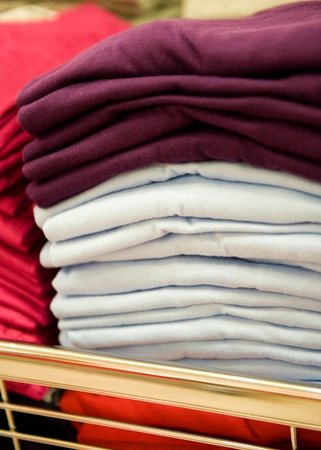 sporting goods: Colorful pile of T-shirts in a shop. Stock Photo