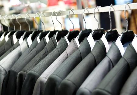 Rangée de costumes pour hommes suspendus dans le placard.