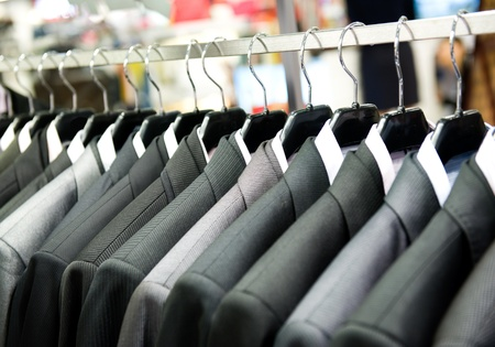 tailor suit: Row of mens suits hanging in closet.