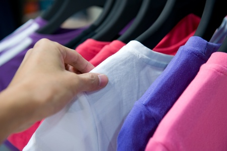 Close-up of a female customer looking for T-shirts in a fashion store  photo