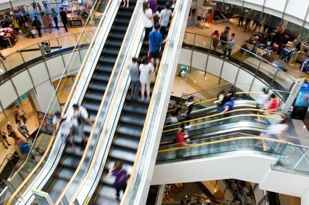 Les populations en mouvement dans des escaliers mécaniques au centre commercial moderne.