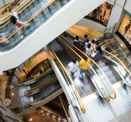 Persone in movimento in scale mobili presso il moderno centro commerciale.