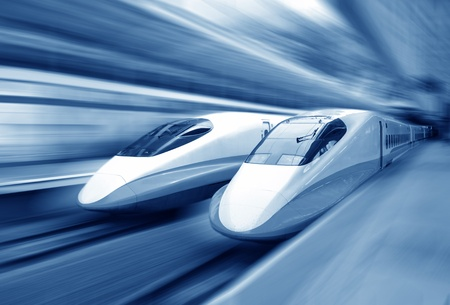 two modern train speeding with motion blur.  Editorial